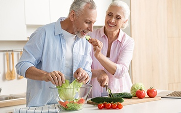 An older couple preparing a salad.