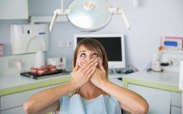 A patient covering her mouth at the dental office.