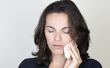 Woman with toothache holding cold compress to face