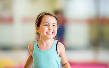 Young girl in teal tank top running