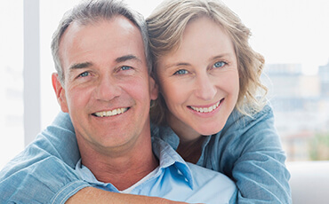 Jacksonville Dental Implants Couple hugging and smiling