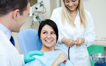 Dentist and assistant helping talking to patient