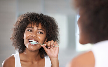 Jacksonville Preventive Dentistry woman brushing teeth in mirror