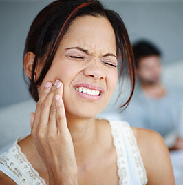 Woman holding her cheek in pain