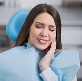 Woman in exam chair holding jaw in pain