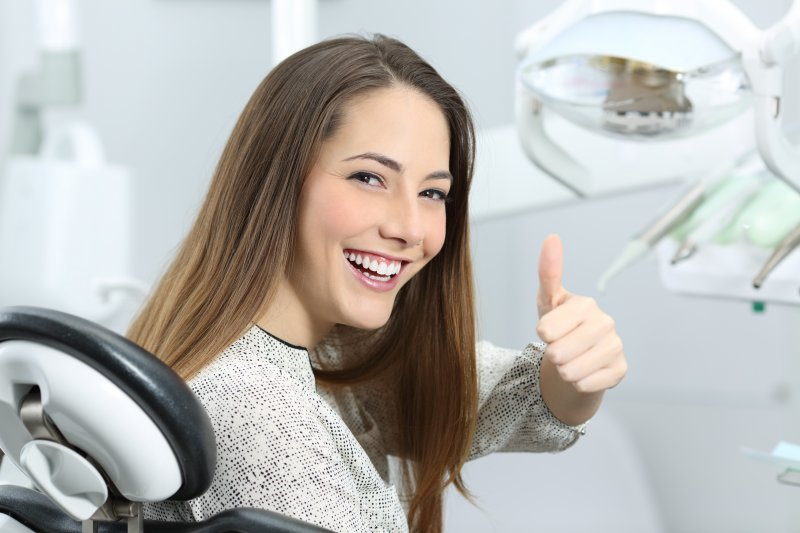woman smiling giving thumb up