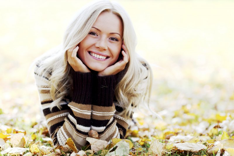 a young woman lying in the leaves smiling