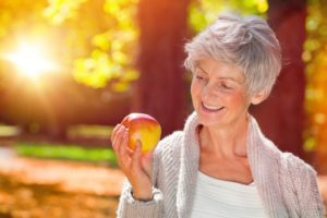Smiling woman holding apple with dentures in Jacksonville