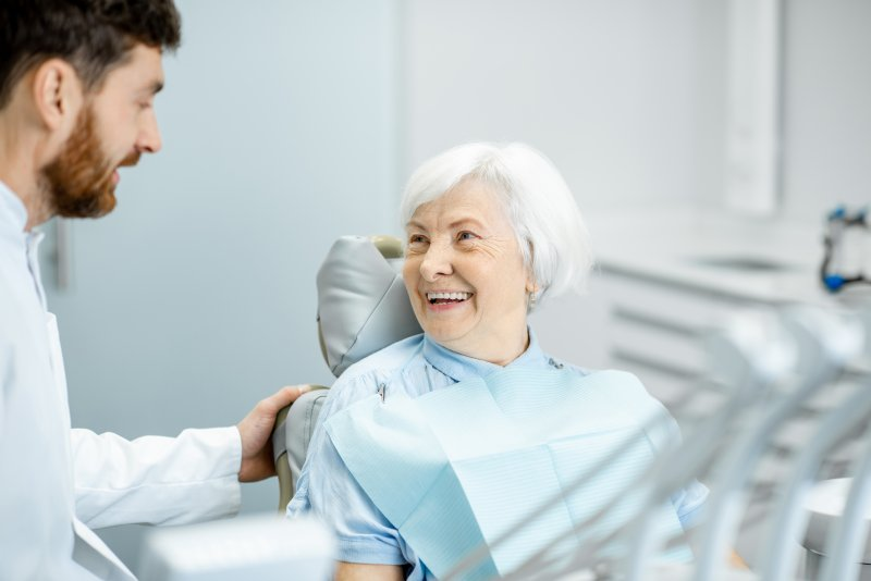 Woman smiling at implant dentist during appointment